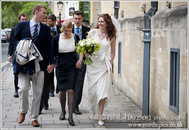Bride & groom walking through Oxford to St John's College